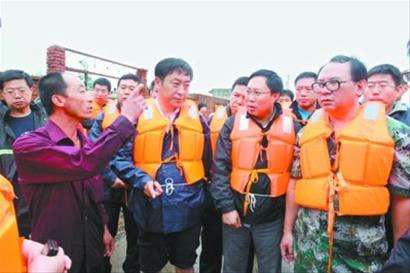 葫芦岛市市长都本伟(右一)和兴城市委书记于学利(前左二)在刘台子乡